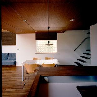 Ispirazione per una sala da pranzo aperta verso il soggiorno moderna con pareti bianche, pavimento in legno massello medio, pavimento marrone e pareti in perlinato