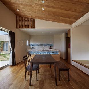 他の地域の大きいおしゃれなリビング (白い壁、暖炉なし、茶色い床、無垢フローリング) の写真