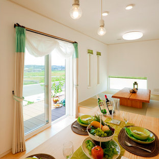 Example of a small zen tatami floor and green floor dining room design in Other with white walls