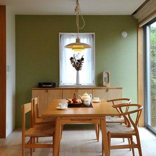 Idee per una sala da pranzo aperta verso il soggiorno minimal di medie dimensioni con pareti verdi, pavimento in compensato e pavimento beige