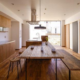 Esempio di una sala da pranzo aperta verso la cucina industriale con pareti bianche, nessun camino e pavimento in legno massello medio