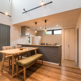 Ispirazione per una piccola sala da pranzo aperta verso la cucina nordica con pareti bianche, pavimento in legno massello medio, nessun camino, pavimento marrone, soffitto in carta da parati e carta da parati