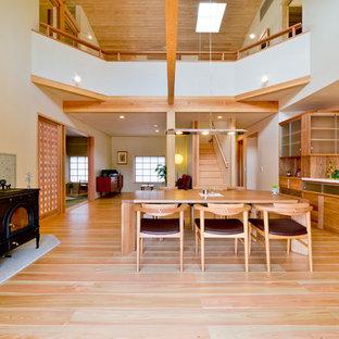 他の地域のアジアンスタイルのおしゃれなLDK (白い壁、淡色無垢フローリング、薪ストーブ、石材の暖炉まわり、茶色い床) の写真