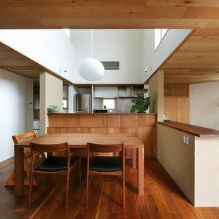 Imagen de comedor moderno, abierto, con paredes blancas, suelo de madera oscura y suelo rosa