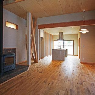 Ispirazione per una sala da pranzo aperta verso il soggiorno etnica con pareti beige, pavimento in legno massello medio, stufa a legna e cornice del camino piastrellata