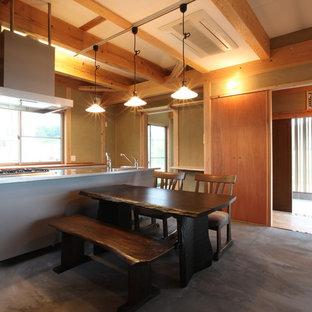 他の地域の中サイズの和風のおしゃれなLDK (茶色い壁、コンクリートの床、薪ストーブ、タイルの暖炉まわり、グレーの床) の写真