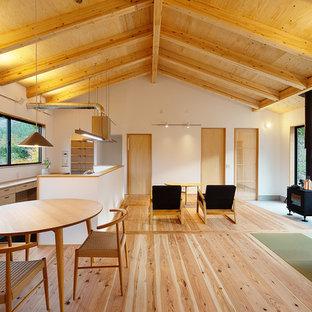 Cette image montre une salle à manger nordique avec un sol de tatami, un poêle à bois et un manteau de cheminée en béton.