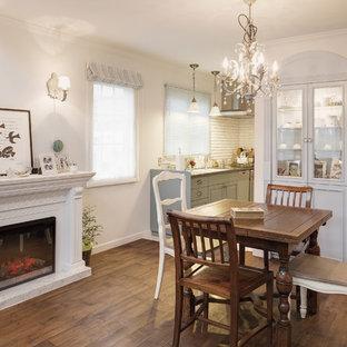 他の地域のトラディショナルスタイルのおしゃれなダイニング (白い壁、無垢フローリング、標準型暖炉、石材の暖炉まわり、茶色い床) の写真