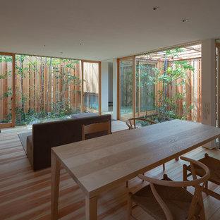 Modelo de comedor asiático, de tamaño medio, abierto, con paredes blancas, suelo de madera pintada, estufa de leña, marco de chimenea de hormigón y suelo marrón