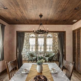 Shabby-Look Esszimmer mit rosa Wandfarbe, braunem Holzboden und braunem Boden in Sonstige