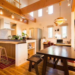 名古屋のアジアンスタイルのおしゃれなダイニングキッチン (白い壁、無垢フローリング、薪ストーブ、レンガの暖炉まわり、茶色い床) の写真