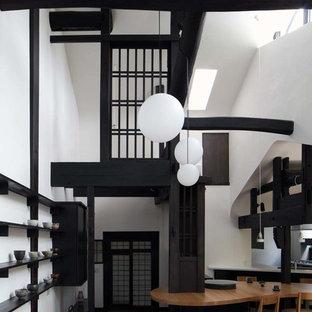 Foto de comedor de cocina de estilo zen con paredes blancas, suelo de madera oscura, estufa de leña, marco de chimenea de piedra y suelo marrón