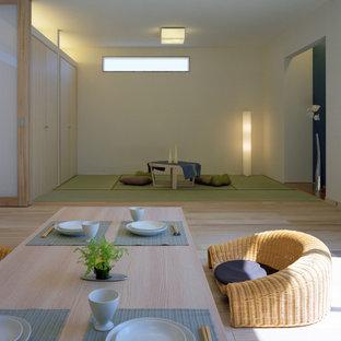 Foto på en orientalisk matplats med öppen planlösning, med vita väggar och ljust trägolv