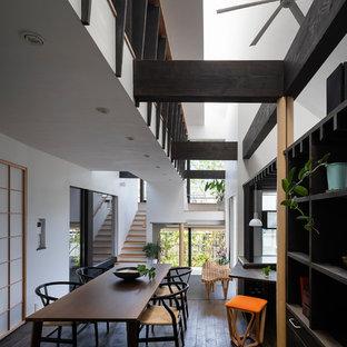 Foto di una sala da pranzo aperta verso il soggiorno etnica con pareti bianche, parquet scuro e pavimento marrone