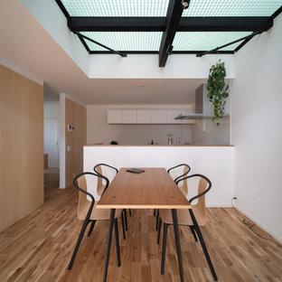 他の地域の中くらいのインダストリアルスタイルのおしゃれなダイニングキッチン (白い壁、淡色無垢フローリング、暖炉なし、茶色い床) の写真