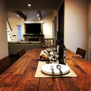 Imagen de comedor escandinavo, abierto, con paredes beige, suelo de madera oscura, chimenea tradicional, marco de chimenea de hormigón y suelo marrón