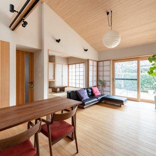 Inredning av en asiatisk mellanstor matplats med öppen planlösning, med vita väggar och ljust trägolv