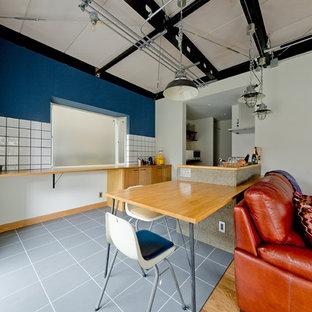 Foto di una sala da pranzo aperta verso il soggiorno industriale con pareti blu, nessun camino e pavimento grigio