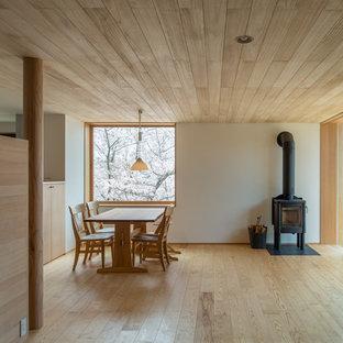 Idéer för en skandinavisk matplats med öppen planlösning, med vita väggar, ljust trägolv, en öppen vedspis och en spiselkrans i metall