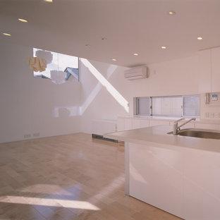 Foto di una sala da pranzo aperta verso il soggiorno minimalista di medie dimensioni con pareti bianche, pavimento in legno massello medio, nessun camino e pavimento rosa