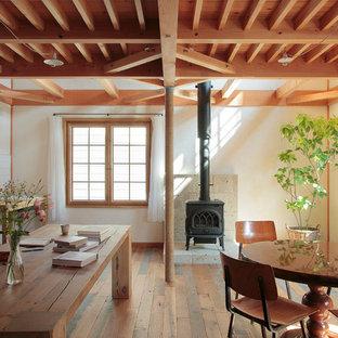 Immagine di una sala da pranzo in campagna con pareti bianche, pavimento in legno massello medio, camino classico e cornice del camino in pietra