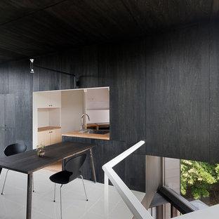 横浜のミッドセンチュリースタイルのおしゃれなダイニング (黒い壁、磁器タイルの床、白い床) の写真