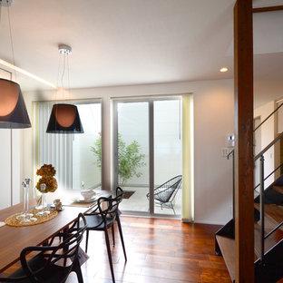 コンテンポラリースタイルのおしゃれなダイニングキッチン (白い壁、無垢フローリング、暖炉なし、茶色い床) の写真