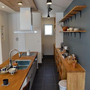他の地域のインダストリアルスタイルのおしゃれなキッチン (シングルシンク、フラットパネル扉のキャビネット、白いキャビネット、木材カウンター、黒い床、茶色いキッチンカウンター) の写真