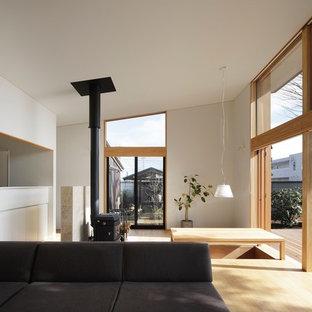 東京23区の広い和風のおしゃれなLDK (白い壁、合板フローリング、薪ストーブ、タイルの暖炉まわり、ベージュの床) の写真