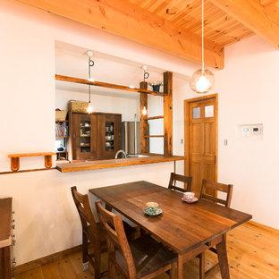 Foto di una sala da pranzo aperta verso il soggiorno etnica con pareti bianche, pavimento in legno massello medio e pavimento marrone