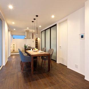 Dining room - scandinavian dark wood floor and brown floor dining room idea in Other with white walls