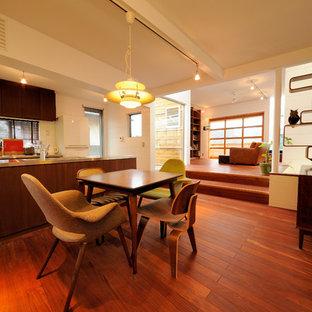Foto di una sala da pranzo aperta verso il soggiorno minimalista con pareti bianche, pavimento in legno verniciato e pavimento marrone