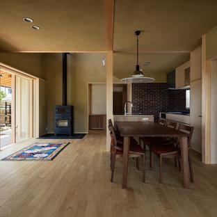 Ispirazione per una sala da pranzo aperta verso il soggiorno etnica con pareti beige, parquet chiaro, stufa a legna, cornice del camino piastrellata e pavimento beige