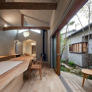 Foto de comedor de cocina de estilo zen con paredes grises, suelo de madera clara, estufa de leña, marco de chimenea de hormigón y suelo beige