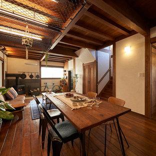 Foto di una sala da pranzo aperta verso il soggiorno etnica con stufa a legna, cornice del camino piastrellata, pareti bianche, pavimento in legno massello medio e pavimento marrone