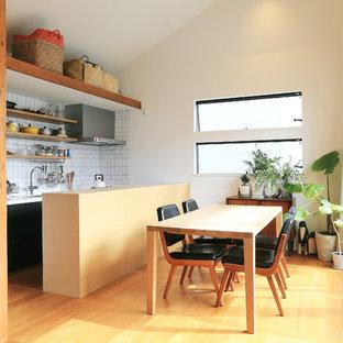Esempio di una piccola sala da pranzo aperta verso la cucina etnica con pareti bianche, pavimento in compensato e pavimento marrone