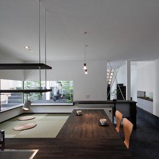 Immagine di una sala da pranzo aperta verso il soggiorno minimalista con pareti bianche, pavimento nero e pavimento in tatami