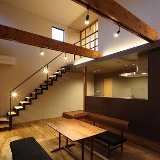 Cette image montre une grande salle à manger ouverte sur le salon asiatique avec un mur blanc, un sol en bois brun et un sol marron.