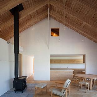 Foto de comedor escandinavo, grande, abierto, con paredes blancas, suelo de madera en tonos medios, chimenea tradicional y marco de chimenea de hormigón