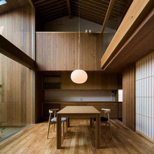 Réalisation d'une salle à manger asiatique avec un mur marron, un sol en bois brun et aucune cheminée.