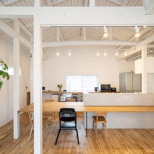Ispirazione per una sala da pranzo aperta verso il soggiorno etnica di medie dimensioni con pareti bianche, pavimento in legno massello medio e pavimento marrone
