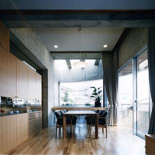 東京23区の大きいインダストリアルスタイルのおしゃれなLDK (グレーの壁、無垢フローリング、暖炉なし、茶色い床、漆喰の暖炉まわり) の写真