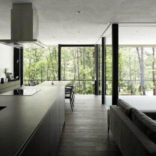Inspiration för moderna matplatser med öppen planlösning, med vita väggar, plywoodgolv, en öppen vedspis, en spiselkrans i gips och brunt golv