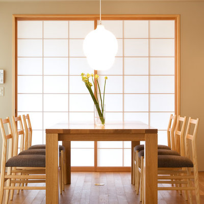 Example of an asian light wood floor and beige floor enclosed dining room design in Other with beige walls and no fireplace