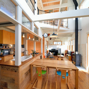 Ispirazione per una sala da pranzo etnica con pavimento in legno massello medio, stufa a legna, cornice del camino piastrellata e pavimento marrone