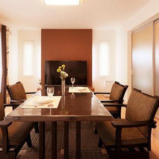 Ispirazione per una grande sala da pranzo aperta verso il soggiorno etnica con pareti marroni, parquet chiaro, nessun camino, cornice del camino piastrellata e pavimento beige