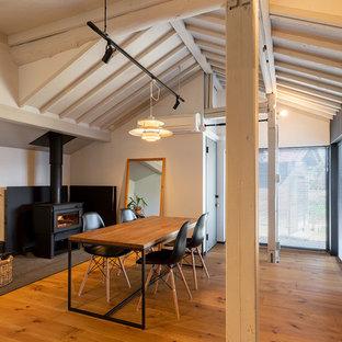 他の地域のインダストリアルスタイルのおしゃれなダイニング (白い壁、無垢フローリング、薪ストーブ、茶色い床) の写真