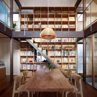 Foto di una sala da pranzo aperta verso la cucina etnica con pavimento in legno massello medio, pavimento marrone e pareti beige