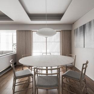 Inredning av en modern mellanstor matplats med öppen planlösning, med plywoodgolv, brunt golv och grå väggar