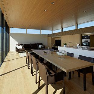 Ispirazione per una sala da pranzo aperta verso il soggiorno moderna con pareti bianche, pavimento beige e pavimento in compensato